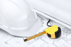 White hard hat and tape measure. Are on the opened design druft Royalty Free Stock Image