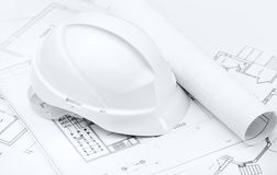 White hard hat on working drawings Stock Photography