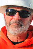 White Hardhat Supervisor. A closeup portrait of an older unshaven laborer wearing a white hardhat, sunglasses and an orange construction caution hooded sweat Stock Photos