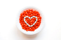 White hart on the top of bowl of pills. Isolated bowl of orange pills with white hart on top stock photos
