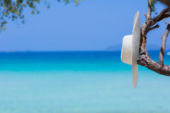 White hat on the beach. White on the beach, blue sea background stock image