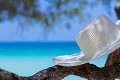 White hat on the beach. White on the beach, blue sea background royalty free stock photography