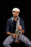 With white hat a black man is sitting and playing his saxophone, dark background, nice music Stock Photo