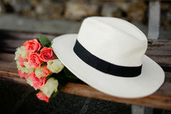White hat and bouquet on the bench stock images