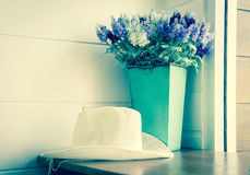 White hat with flowers vase,vintage filtered. Stock Photos