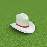 White hat with a red ribbon on a green grass background Royalty Free Stock Photos