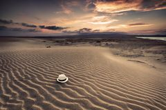 White hat. A white hat on the sand, under cloudy sky Stock Photos