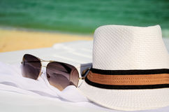 White hat and sunglasses on the background of sea and sand Royalty Free Stock Images