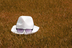 White hat and sunglasses dry grass Stock Image