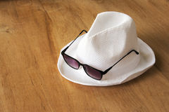 White hat and sunglasses dry grass on wood table Royalty Free Stock Photography