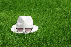 White hat and sunglasses fresh grass on autumn Royalty Free Stock Photo