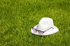 White hat and sunglasses on the green grass background Royalty Free Stock Image