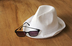 White hat and sunglasses on wood table Stock Photography