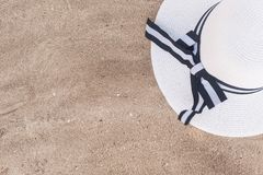 A white hat with wide brim and a seashell lie on the fine light sand. Background with beach accessories.  royalty free stock image