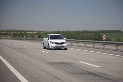 White hatchback rides on the highway royalty free stock photos