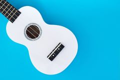 White Hawaiian guitar, ukulele on a blue background. Musical concept. Flat Lay Template. Place for text.  Stock Photos