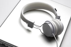 White headfones on laptop. Royalty Free Stock Photography