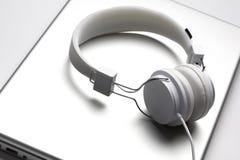 White headfones on laptop. Royalty Free Stock Photography