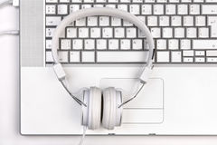 White headfones on silver laptop. Royalty Free Stock Image