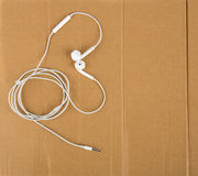 White headphone wires in the form of heart on cardboard. Love Music Royalty Free Stock Image