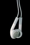 White headphones on black background. This is a pair of white headphone or earbuds photographed on a black background Royalty Free Stock Photos