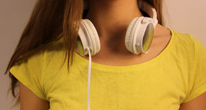 White headphones close-up hanging on the neck of the young girl in a yellow T-shirt Royalty Free Stock Photo