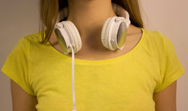 White headphones close-up hanging on the neck of the young girl in a yellow T-shirt Stock Photography