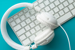 White headphones and computer keyboard. Stock Images