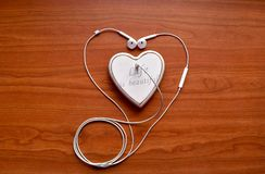 A white headphones connected to the white heart. A white headphones connected to white polymer clay heart on the wood background with love is beautiful written Royalty Free Stock Image