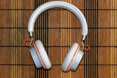 White headphones with orange braid on wooden background. For web site or mobile devices Royalty Free Stock Photos