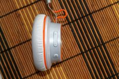 White headphones with orange braid on wooden background. For web site or mobile devices Royalty Free Stock Photo