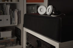 White headphones over central speakers from a 7.1 THX Hi-Fi sound system Stock Photo