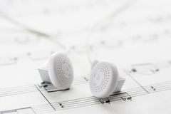 White headphones on sheet music Royalty Free Stock Photos
