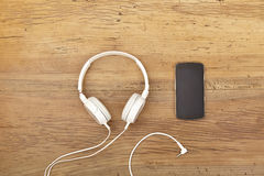 White headphones and smart phone on wood Stock Photography