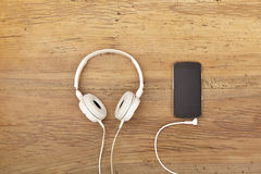 White headphones and smart phone on wood Royalty Free Stock Photos