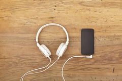 White headphones and smart phone on wood Stock Photos