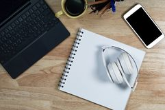 White headphones stack on white book paper on the wooden table stock photography