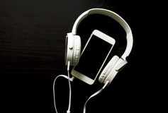 White smartphone and headphones banner template with text place. White headphones and telephone on black. White smartphone and headphones banner template with Royalty Free Stock Images