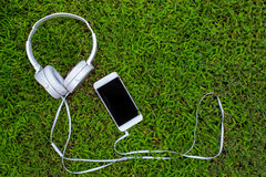 White headphones and white smartphone on green grass. Summer lawn with personal gadget. Stock Photo