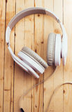 White headphones on a wooden background Stock Images