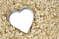 White heart on a bed of oatmeal. Tilted white heart outlined with silver on a bed of oatmeal; white heart can be filled with text royalty free stock photography