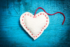 White heart on the blue boards. Valentine`s Day. Colorful knitted hearts. White heart on the blue boards. Valentines day. Heart pendant. Red heart. Valentine Stock Photography