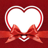 White heart border frame with red ribbon bow on red Stock Image