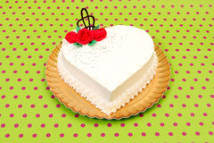White heart cake. With red marzipan roses on dotted background. Copy space on cake Stock Photos
