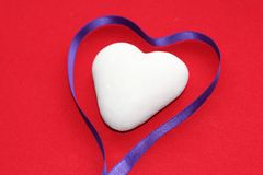 White heart on a colored background in honor of Valentine`s Day stock photo