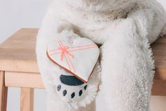 White heart gingerbread on paw of old bear toy on wooden chair on grey background. The White heart gingerbread on paw of old bear toy on wooden chair on grey stock image