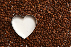White heart made with coffee beans. Coffee beans lying around white heart. Free space. Horizontal. Flat Royalty Free Stock Photos