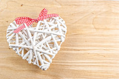 White heart made from willow with red ribbon on wooden background Stock Image