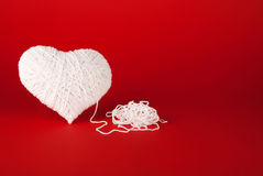 White heart made of wool on a red background. Royalty Free Stock Images