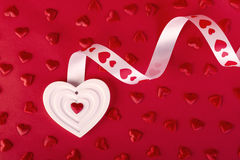 White heart with ribbon and red hearts on red Stock Photo